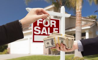Agent Handing Over Keys as Buyer is Handing Over Cash for House with Home and For Sale Real Estate Sign Behind.